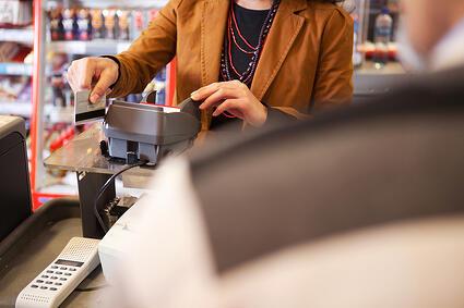 bigstock-Shop-assistant-swiping-credit--29756006